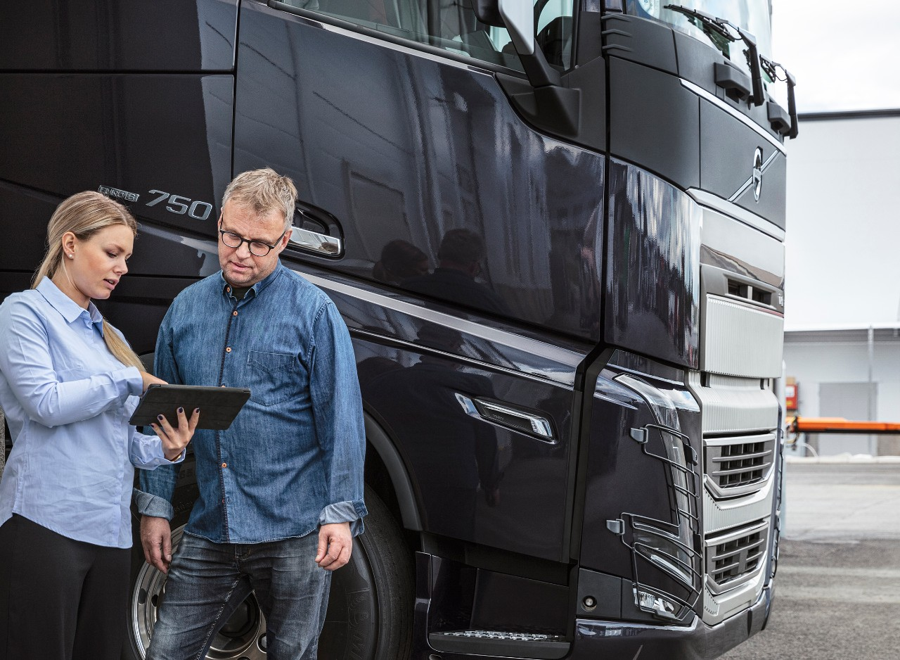 Un hombre y una mujer delante de un camión mirando una tablet