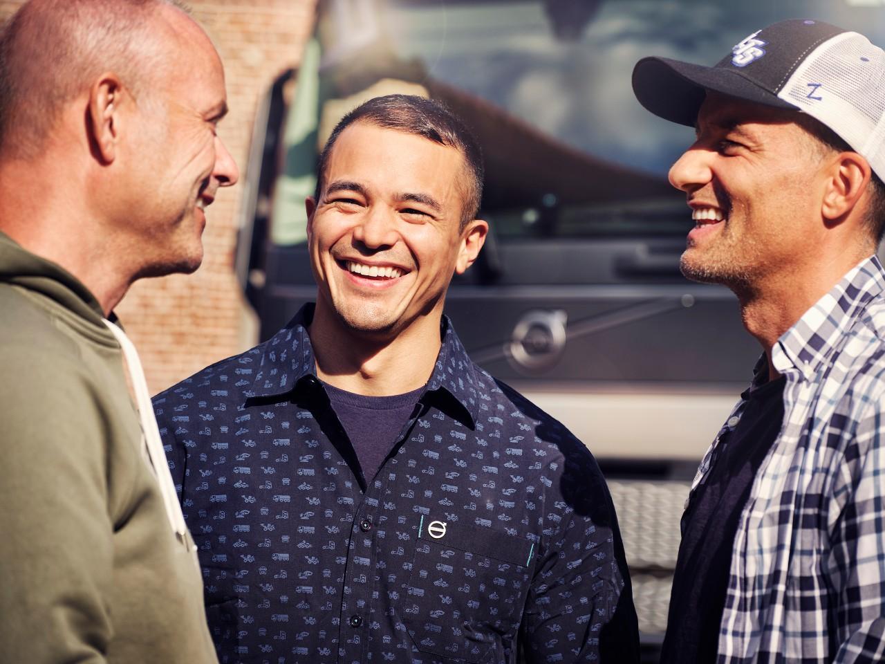 Un primer plano de tres hombres sonriendo delante de un camión Volvo